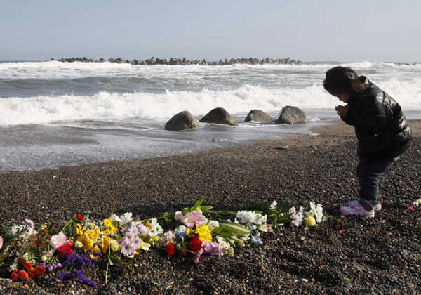 A girl offers prayers for victims of the March 11, 2011 earthquake and tsunami